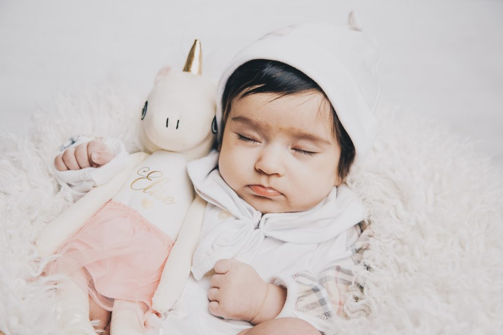 Nyfödd bebis med enhörnings gosedjur sover